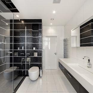 Неиссякаемый источник вдохновения для домашнего уюта: ванная комната в современном стиле с плоскими фасадами, черными фасадами, угловым душем, инсталляцией, черной плиткой, белой плиткой, плиткой мозаикой, белыми стенами, монолитной раковиной, белым полом, душем с раздвижными дверями и белой столешницей