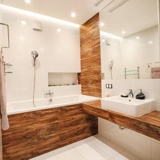 Стильный дизайн: ванная комната в современном стиле с ванной в нише, душем над ванной, белыми стенами, белой плиткой, керамической плиткой, полом из керамической плитки, столешницей из дерева, настольной раковиной и коричневой столешницей - последний тренд