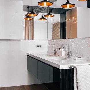 На фото: ванные комнаты в современном стиле с плоскими фасадами, черными фасадами, врезной раковиной, коричневым полом и белой столешницей