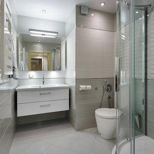 На фото: ванная комната среднего размера в современном стиле с угловым душем, раздельным унитазом, серой плиткой, керамической плиткой, серыми стенами, полом из керамической плитки, душевой кабиной, подвесной раковиной, белым полом и душем с раздвижными дверями с