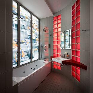 Modelo de cuarto de baño principal, contemporáneo, con armarios abiertos, combinación de ducha y bañera, baldosas y/o azulejos grises, lavabo integrado, puertas de armario de madera en tonos medios, bañera encastrada, paredes beige y ducha abierta