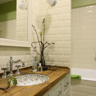 На фото: ванные комнаты в стиле кантри с белыми фасадами, ванной в нише, душем над ванной, бежевой плиткой, плиткой кабанчик, зелеными стенами, врезной раковиной и столешницей из дерева