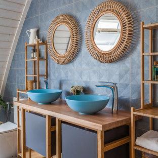 Новый формат декора квартиры: ванная комната в современном стиле с серой плиткой, белыми стенами, настольной раковиной, столешницей из дерева, серым полом, плоскими фасадами и коричневой столешницей