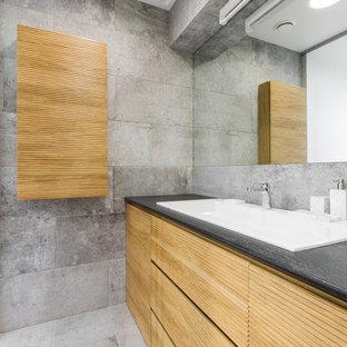На фото: ванная комната среднего размера в скандинавском стиле с светлыми деревянными фасадами, серой плиткой, керамогранитной плиткой, полом из керамогранита, душевой кабиной, столешницей из искусственного кварца, накладной раковиной, фасадами с филенкой типа жалюзи и серыми стенами с