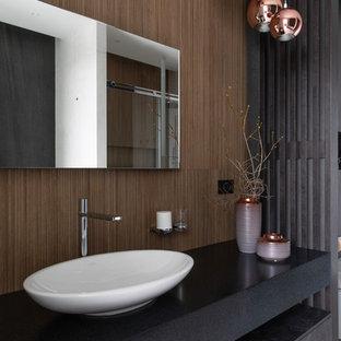 Идея дизайна: ванная комната в современном стиле с плоскими фасадами, черными фасадами, коричневыми стенами, настольной раковиной, белым полом и черной столешницей