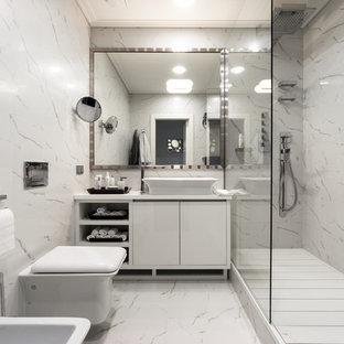 На фото: ванные комнаты в современном стиле с плоскими фасадами, белыми фасадами, душем в нише, биде, белой плиткой, мраморным полом, душевой кабиной и настольной раковиной