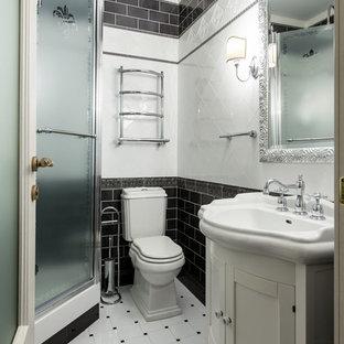 Стильный дизайн: ванная комната в классическом стиле с фасадами в стиле шейкер, белыми фасадами, угловым душем, раздельным унитазом, белой плиткой, черной плиткой, душевой кабиной, монолитной раковиной, белым полом и душем с распашными дверями - последний тренд