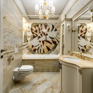 Пример оригинального дизайна: главная ванная комната в классическом стиле с накладной ванной, инсталляцией, бежевой плиткой, врезной раковиной, бежевым полом и бежевой столешницей