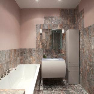 Esempio di una stanza da bagno padronale design di medie dimensioni con ante lisce, doccia ad angolo, piastrelle rosa, piastrelle in pietra, pareti rosa, pavimento in marmo, top in vetro, ante grigie, vasca da incasso e lavabo sottopiano