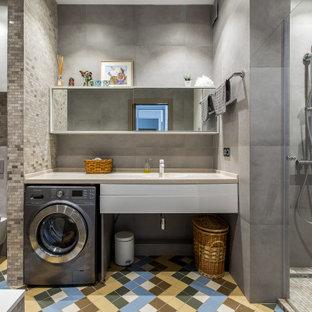 На фото: ванная комната в современном стиле с белыми фасадами, душем в нише, серой плиткой, врезной раковиной, разноцветным полом, бежевой столешницей и стиральной машиной с