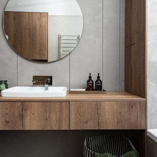 Стильный дизайн: ванная комната среднего размера в современном стиле с плоскими фасадами, фасадами цвета дерева среднего тона, серой плиткой, керамогранитной плиткой, коричневыми стенами, полом из керамогранита, душевой кабиной, накладной раковиной, столешницей из дерева, серым полом, коричневой столешницей, тумбой под одну раковину и встроенной тумбой - последний тренд