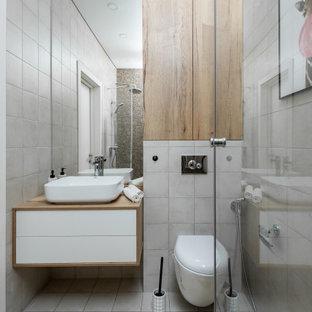 Ejemplo de cuarto de baño con ducha y madera, actual, de tamaño medio, madera, con armarios con paneles lisos, puertas de armario blancas, baldosas y/o azulejos grises, baldosas y/o azulejos de porcelana, suelo de baldosas de porcelana, lavabo sobreencimera, encimera de madera, suelo gris, encimeras beige y madera