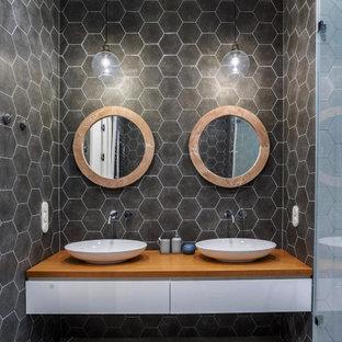 Пример оригинального дизайна: ванная комната среднего размера в современном стиле с плоскими фасадами, белыми фасадами, серой плиткой, душевой кабиной, настольной раковиной, столешницей из дерева, серым полом, коричневой столешницей и подвесной тумбой