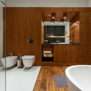 На фото: главные ванные комнаты в современном стиле с плоскими фасадами, фасадами цвета дерева среднего тона, отдельно стоящей ванной и инсталляцией
