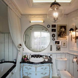 На фото: главная ванная комната в стиле современная классика с синими фасадами, полновстраиваемой ванной, белыми стенами, накладной раковиной и черной столешницей с