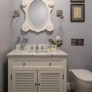 Стильный дизайн: ванная комната среднего размера в классическом стиле с серыми стенами, полом из керамической плитки, серым полом, фасадами с филенкой типа жалюзи, белыми фасадами, раздельным унитазом, мраморной столешницей и врезной раковиной - последний тренд