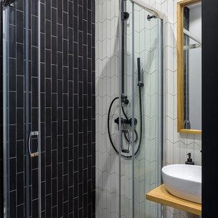 モスクワの小さい北欧スタイルのおしゃれなバスルーム (浴槽なし) (オープンシェルフ、淡色木目調キャビネット、コーナー設置型シャワー、セラミックタイル、セラミックタイルの床、木製洗面台、マルチカラーの床、引戸のシャワー、白いタイル、黒いタイル、ベッセル式洗面器) の写真