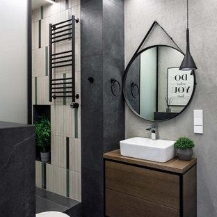 Пример оригинального дизайна: ванная комната в скандинавском стиле с коричневыми фасадами, душем в нише, разноцветной плиткой, серыми стенами, душевой кабиной, настольной раковиной, черным полом и коричневой столешницей