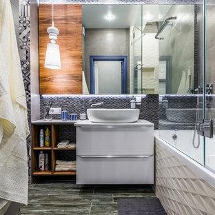 На фото: главная ванная комната в современном стиле с плоскими фасадами, белыми фасадами, накладной ванной, душем над ванной, серой плиткой, настольной раковиной, серым полом, душем с раздвижными дверями и серой столешницей с
