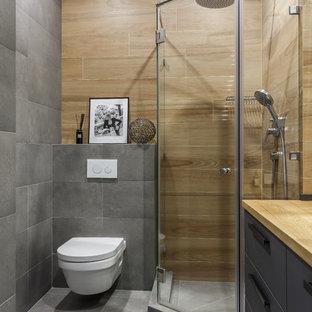 Ispirazione per una stanza da bagno design con ante lisce, ante grigie, doccia ad angolo, WC sospeso, piastrelle marroni, piastrelle grigie, top in legno, pavimento grigio, porta doccia a battente e top marrone