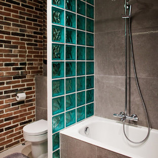Cette image montre une salle de bain principale urbaine avec une baignoire en alcôve, un combiné douche/baignoire, un WC séparé, un carrelage gris, un mur marron et une cabine de douche avec un rideau.