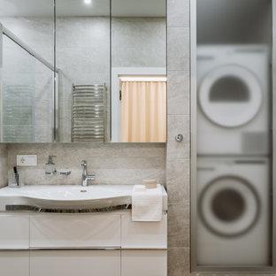 На фото: ванная комната среднего размера в современном стиле с плоскими фасадами, белыми фасадами, душем в нише, серой плиткой, керамогранитной плиткой, душевой кабиной, монолитной раковиной, коричневым полом, душем с раздвижными дверями и белой столешницей