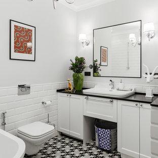 На фото: ванная комната среднего размера в стиле неоклассика (современная классика) с фасадами с утопленной филенкой, белыми фасадами, инсталляцией, белой плиткой, керамической плиткой, серыми стенами, полом из керамической плитки, накладной раковиной, столешницей из искусственного камня, разноцветным полом и черной столешницей