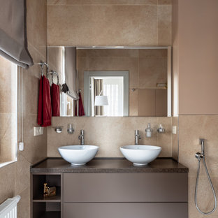 Пример оригинального дизайна: ванная комната среднего размера в современном стиле с плоскими фасадами, коричневыми фасадами, бежевой плиткой, керамогранитной плиткой, бежевыми стенами, полом из керамогранита, душевой кабиной, настольной раковиной, столешницей из гранита, серым полом и коричневой столешницей