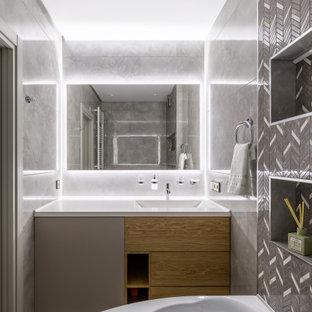 Пример оригинального дизайна: ванная комната среднего размера в современном стиле с плоскими фасадами, светлыми деревянными фасадами, гидромассажной ванной, душем над ванной, серой плиткой, душевой кабиной, монолитной раковиной, открытым душем и белой столешницей