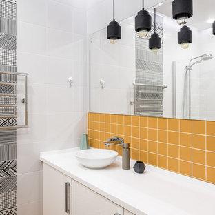 Пример оригинального дизайна: главная ванная комната среднего размера в современном стиле с белой плиткой, разноцветной плиткой, желтой плиткой, керамической плиткой, плоскими фасадами, белыми фасадами, полом из керамической плитки, настольной раковиной, желтым полом и белой столешницей