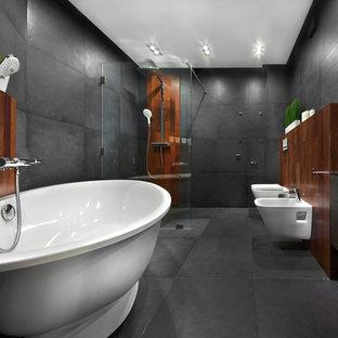 Создайте стильный интерьер: главная ванная комната в современном стиле с плоскими фасадами, темными деревянными фасадами, отдельно стоящей ванной, душем без бортиков, биде, серой плиткой, настольной раковиной, серым полом и открытым душем - последний тренд