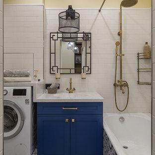 Imagen de cuarto de baño principal, actual, con armarios con paneles empotrados, puertas de armario azules, bañera empotrada, combinación de ducha y bañera, baldosas y/o azulejos blancos, paredes amarillas, suelo multicolor, ducha con cortina y encimeras blancas