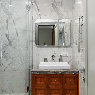 На фото: ванная комната в стиле современная классика с фасадами с утопленной филенкой, фасадами цвета дерева среднего тона, угловым душем, серой плиткой, душевой кабиной, накладной раковиной, серым полом и душем с распашными дверями с