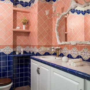 Idee per una stanza da bagno chic con ante con bugna sagomata, ante bianche, piastrelle blu, piastrelle rosa, lavabo da incasso e top piastrellato