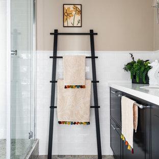 Свежая идея для дизайна: ванная комната среднего размера в стиле неоклассика (современная классика) с плоскими фасадами, черными фасадами, душем в нише, белой плиткой, бежевыми стенами, душевой кабиной, врезной раковиной, серым полом, душем с распашными дверями, белой столешницей, тумбой под одну раковину и встроенной тумбой - отличное фото интерьера