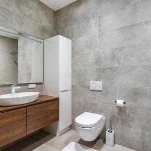 Стильный дизайн: ванная комната в современном стиле с плоскими фасадами, темными деревянными фасадами, ванной в нише, душем над ванной, серой плиткой, душевой кабиной, настольной раковиной, столешницей из дерева, серым полом и коричневой столешницей - последний тренд