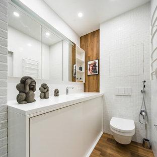 На фото: ванные комнаты в современном стиле с плоскими фасадами, белыми фасадами, инсталляцией, белой плиткой, коричневым полом и белой столешницей