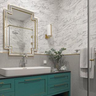 Ejemplo de cuarto de baño tradicional renovado con armarios con paneles empotrados, baldosas y/o azulejos grises, lavabo sobreencimera, suelo gris, encimeras negras, puertas de armario turquesas, paredes grises, suelo de baldosas de porcelana y encimera de acrílico