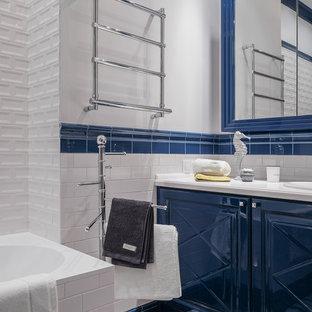 Новые идеи обустройства дома: ванная комната среднего размера в стиле современная классика с синими фасадами, душем над ванной, белой плиткой, керамической плиткой, белыми стенами, полом из керамогранита, накладной раковиной, столешницей из искусственного камня, разноцветным полом, фасадами с выступающей филенкой, накладной ванной, душевой кабиной и открытым душем