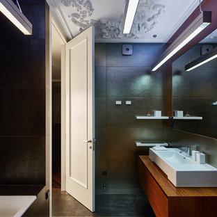 Imagen de cuarto de baño principal, actual, de tamaño medio, con armarios con paneles lisos, puertas de armario marrones, bañera encastrada sin remate, sanitario de pared, baldosas y/o azulejos grises, baldosas y/o azulejos de metal, paredes grises, suelo de madera en tonos medios, lavabo sobreencimera y encimera de madera