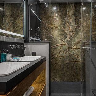 Пример оригинального дизайна: ванная комната в современном стиле с плоскими фасадами, фасадами цвета дерева среднего тона, душем в нише, душевой кабиной, накладной раковиной, черным полом, душем с распашными дверями и черной столешницей