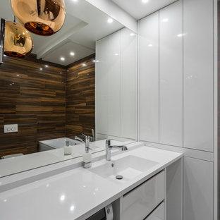 Inredning av ett modernt badrum, med släta luckor, vita skåp, brun kakel, ett integrerad handfat och vitt golv