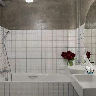 Удачное сочетание для дизайна помещения: главная ванная комната в современном стиле с ванной в нише, душем над ванной, белой плиткой, серыми стенами, настольной раковиной и белым полом - самое интересное для вас