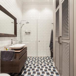 На фото: ванные комнаты в стиле современная классика с плоскими фасадами, фасадами цвета дерева среднего тона, душем без бортиков, белой плиткой, плиткой кабанчик, полом из керамогранита, душевой кабиной, настольной раковиной, разноцветным полом и душем с распашными дверями