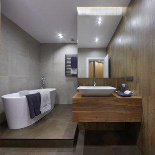 Новые идеи обустройства дома: главная ванная комната в современном стиле с плоскими фасадами, фасадами цвета дерева среднего тона, отдельно стоящей ванной, серой плиткой, настольной раковиной, цементной плиткой, столешницей из дерева, серым полом и коричневой столешницей