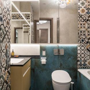 Cette image montre une salle d'eau design de taille moyenne avec un placard à porte plane, des portes de placard jaunes, une baignoire encastrée, un combiné douche/baignoire, un WC suspendu, un carrelage multicolore, un sol en carrelage de porcelaine, un plan de toilette en surface solide, un sol turquoise, aucune cabine et un plan de toilette noir.