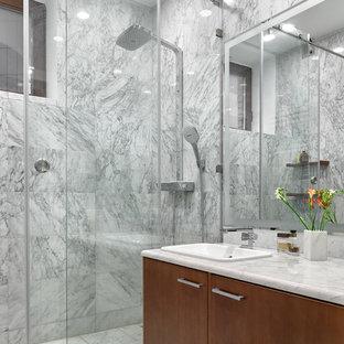На фото: ванная комната в современном стиле с плоскими фасадами, фасадами цвета дерева среднего тона, душем в нише, серой плиткой, каменной плиткой, мраморным полом, душевой кабиной, накладной раковиной, мраморной столешницей и душем с раздвижными дверями с