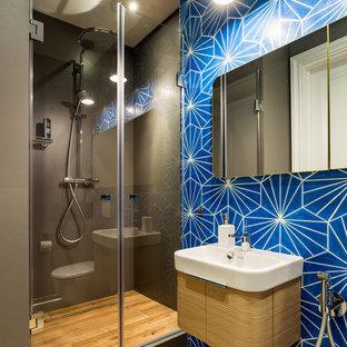 Immagine di una stanza da bagno con doccia design di medie dimensioni con ante lisce, ante in legno chiaro, doccia alcova, WC sospeso, piastrelle blu, piastrelle in ceramica, pareti blu, pavimento con piastrelle in ceramica, lavabo a consolle, top in legno, pavimento marrone e porta doccia a battente