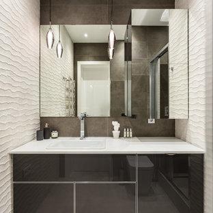 Новый формат декора квартиры: ванная комната в современном стиле с плоскими фасадами, черными фасадами, накладной раковиной, серым полом, белой столешницей, коричневой плиткой и бежевыми стенами