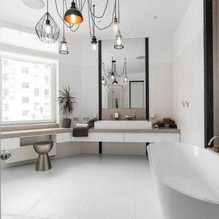 Пример оригинального дизайна интерьера: главная ванная комната в современном стиле с плоскими фасадами, белыми фасадами, отдельно стоящей ванной, белой плиткой, белыми стенами и раковиной с несколькими смесителями